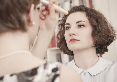 Two young women applying retro style make up - DISF000751
