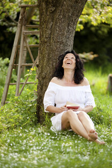 Germany, mature woman relaxing under tree reading book - CvKF000025