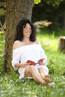 Germany, mature woman relaxing under tree reading book - CvKF000026