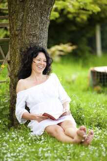 Germany, mature woman relaxing under tree reading book - CvKF000027