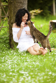 Germany, mature woman with cat under tree - CvKF000028