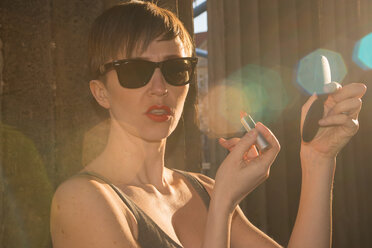 Germany, Berlin, portrait of woman with sunglasses putting lipstick on - FBF000318