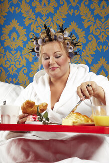 Woman with curlers and white bathrobe having breakfast in bed - CSBF000005