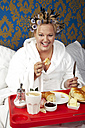 Portrait of woman with curlers and white bathrobe having breakfast in bed - CSBF000011