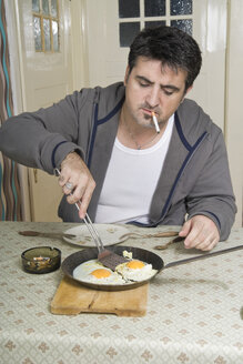 Portrait of man with bad habit sitting at breakfast table - CSBF000017