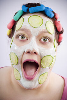 Portrait of screaming woman wearing curlers and beauty mask with slices of cucumber - CSBF000024