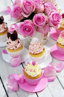 Cupcakes and flower vase of pink roses on wooden table - CSF021212