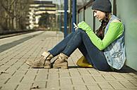 Teenage girl using smartphone at platform - UUF000195