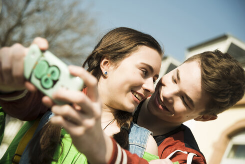 Portrait of teenage couple photographing themselves with smartphone - UUF000202