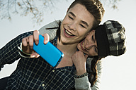 Portrait of teenage couple photographing themselves with smartphone - UUF000207