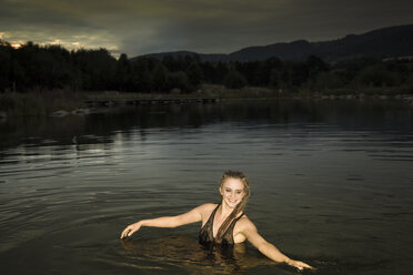 Young woman bathing with evening dress in lake at dawn - FCF000015