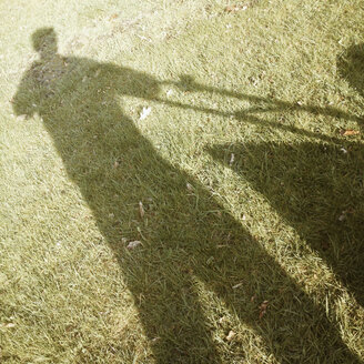 Germany, North Rhine-Westphalia, Petershagen, Shadow of a man with a lawn mower. - HAWF000083