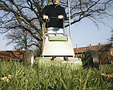 Germany, North Rhine-Westphalia, Petershagen, Man mowing a lawn with an old electric lawn mover. - HAWF000088