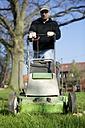 Germany, Petershagen, Man mowing lawn - HAWF000093