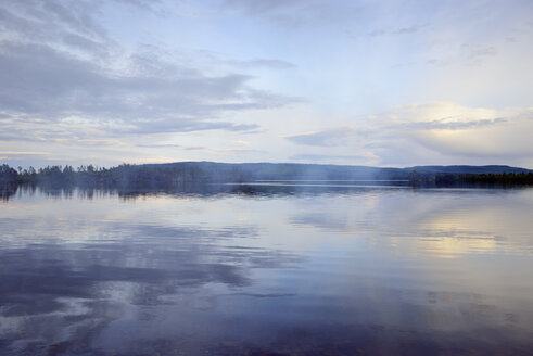 Sweden, Stroemsund, Sunset at a lake and smoke from a campfire - BR000530