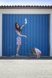 Young woman with little daughter in front of blue garage door - MW000045
