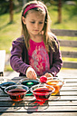 Germany, Bavaria, Landshut, Girl dyeing Easter eggs - SARF000447