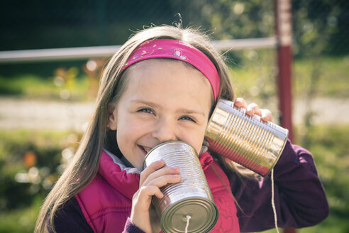 Portait of little girl with tin can phone - SARF000470
