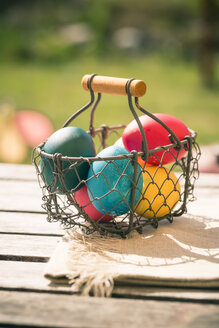 Germany, Colorful Easter eggs on wooden table - SARF000458