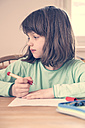 Portrait of little girl doing homework - LVF001042