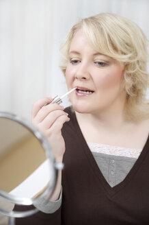 Blond woman applying make up - ECF000541