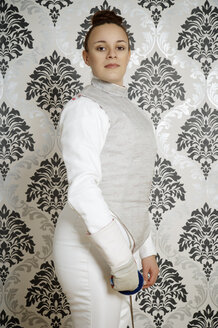 Portrait of young female fencer with floret in front of checkered wallpaper - ECF000532