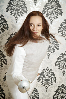 Portrait of young female fencer with floret in front of checkered wallpaper - ECF000529