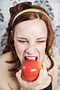 Portrait of young woman eating red apple - ECF000523