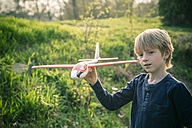 Germany, Bavaria, Landshut, Boy playing with toy aeroplane - SARF000478