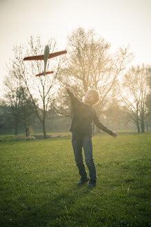 Germany, Bavaria, Landshut, Boy playing with toy aeroplane - SARF000480