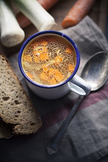 Homemade chicken broth in cup with slices of bread and ingredients - SBDF000783
