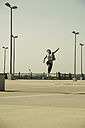 Young woman with skateboard jumping on parking level - UUF000223