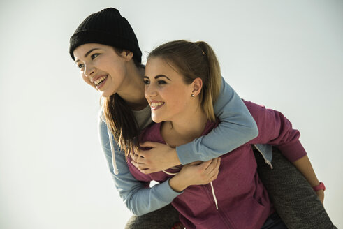 Happy young woman carrying friend piggyback - UUF000245