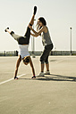 Young woman practicing handstand assisted by a friend - UUF000254