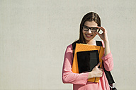 Brunette young woman with bag, folder and digital tablet outdoors - UUF000306