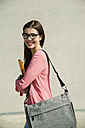 Brunette young woman with bag, folder and digital tablet outdoors - UUF000270