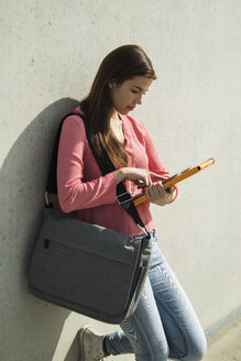Brunette young woman using digital tablet outdoors - UUF000305