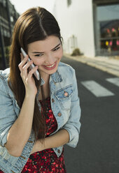 Brunette young woman using cell phone outdoors - UUF000278