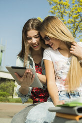 Two happy young women using digital tablet outdoors - UUF000304