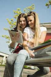 Two happy young women using digital tablet outdoors - UUF000303