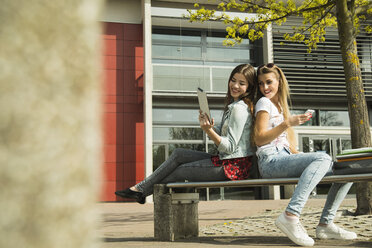 Two happy young women using digital tablet and cell phone outdoors - UUF000302