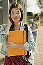 Smiling brunette young woman with  folder outdoors - UUF000288