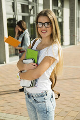 Smiling blond young woman with  folder outdoors - UUF000299
