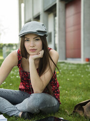 Brunette young woman sitting on meadow - UUF000295