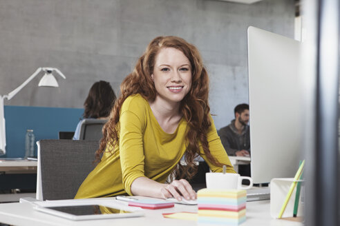 Portrait of smiling woman at her workplace in the open space office - RBF001615