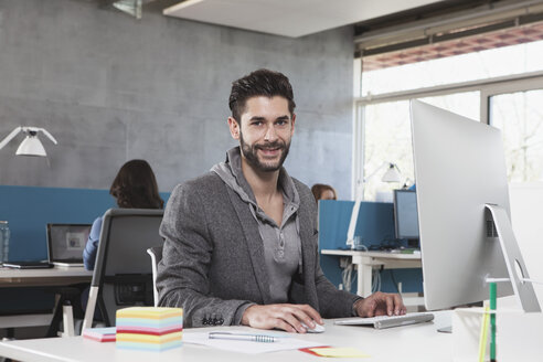 Portrait of smiling man at his workplace in the office - RBF001617