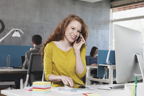 Portrait of smiling woman telephoning with smartphone at her workplace in the open space office - RBF001682