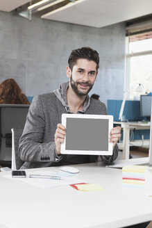 Portrait of smiling man showing tablet computer in the office - RBF001622