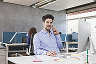 Portrait of man telephoning with his smartphone at his workplace in the office - RBF001626