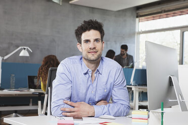 Portrait of smiling man at his workplace in the office - RBF001630